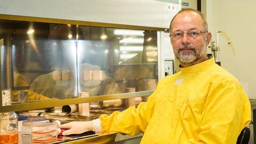 Virologe Prof. Andreas Dotzauer sitzt in einem Schutzanzug im Labor