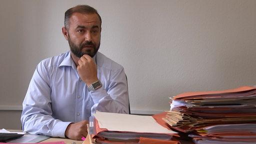Ein türkischer Anwalt sitzt am Schreibtisch, vor ihm mehrere Mappen.
