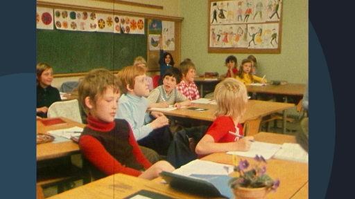 Archivbild: Eine volle Schulklasse mit vielen Kindern, die an Tischen sitzen.