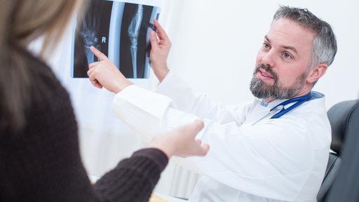 Ein Arzt bespricht eine Röntgen-Aufnahme mit einer Patientin