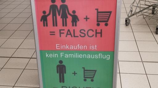 Ein Aufsteller in einem Supermarkt, dass pro Einkauf eine Person erlaubt ist.