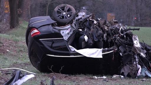 Ein völlig zerstörtes Auto liegt nach einem Unfall auf dem Dach.
