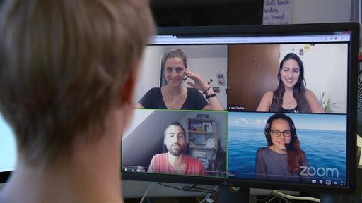 Frau schaut auf  Bildschirm, auf dem vier junge Menschen über Zoom chatten