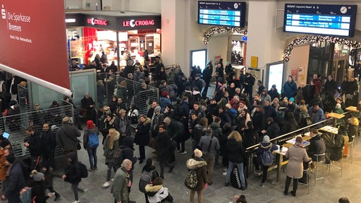 Bahnreisende warten wegen des Streiks in der Halle des Bremer Hauptbahnhofs auf Informationen.