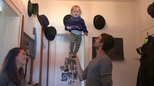 Ein Mann balanciert ein Kleinkind auf seiner Hand.