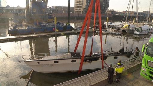 Eine Yacht wird aus einem Gewässen gehoben