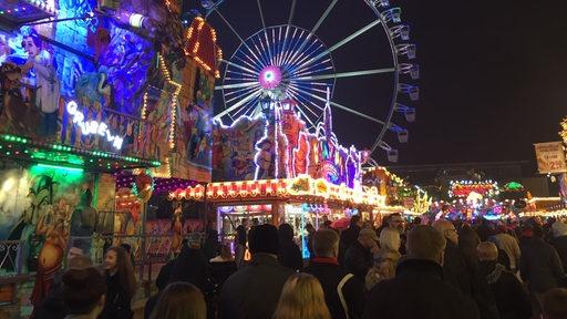 Das bunt beleuchtete Riesenrad vor schwarzem Himmel. Davor viele Menschen beim letzten Abend des Bremer Freimarkts.