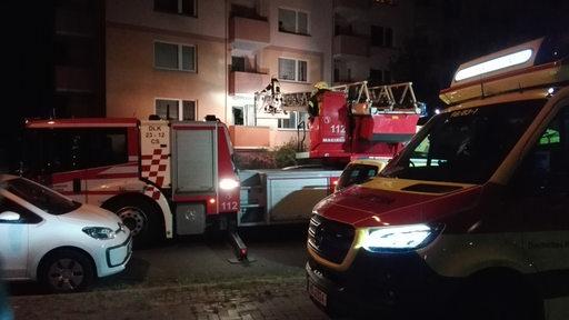 Feuerwehrautos stehen vor einem Haus. Ein Feuerwehrmann steht auf einer Drehleiter.