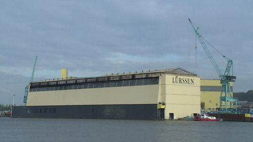 Die gelbliche Halle der Lürssen Werft und ein grünlicher Kran sind zu sehen.