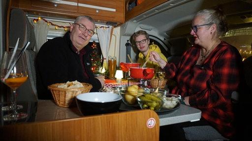 Zwei Männer und eine Frau essen Käse-Fondue in einem Wohnmobil