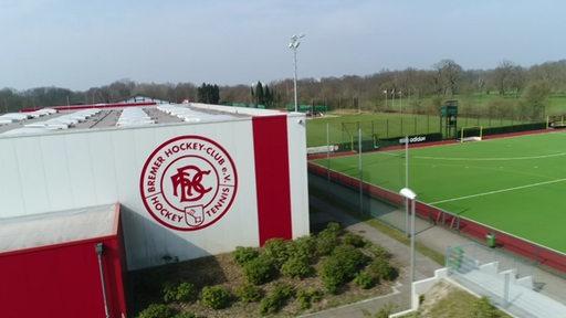 Luftbild: Gebäude und Sportanlagen des Bremer HC. An der Wand das Logo.