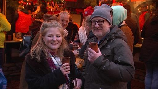 Zwei Briten, die auf dem Bremer Weihnachtsmarkt stehen.