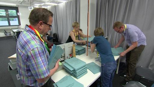 Wahlhelfer zählen die Stimmen aus. Zu sehen sind zwei damen und zwei Herren.