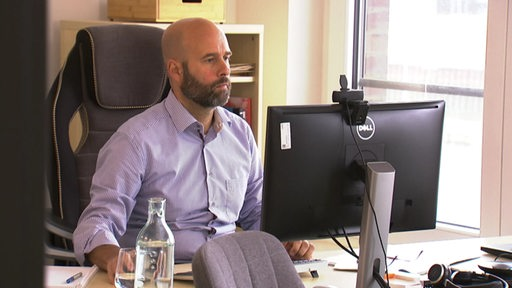 Ein Mann sitzt an einem Schreibtisch und arbeitet an einem Computer.