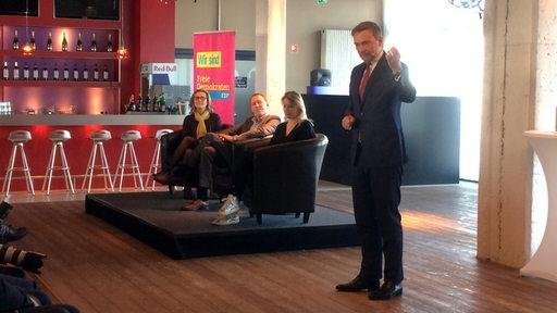 FDP-Bundeschef Christian Lindner steht in einem großen Raum und spricht zu Menschen. Im Hintergrund Lencke Steiner, Fraktionschefin der FDP in Bremen.