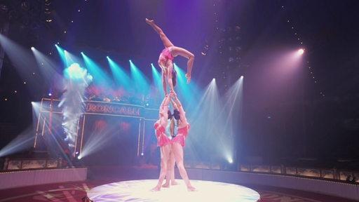 Drei Akrobatinnen turnen eine Figur im Circus Roncalli.