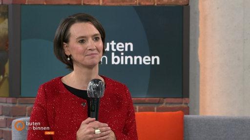 Bildungssenatorin Claudia Bogedan mit einem Mikrofon in der Hand im buten un binnen-Studio.