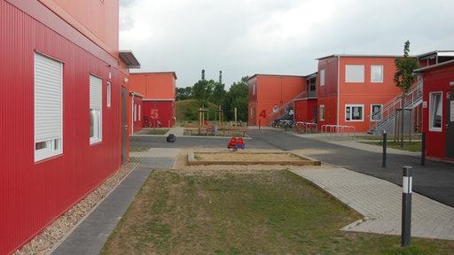 Containerdorf mit rot-orangenen Elementen.