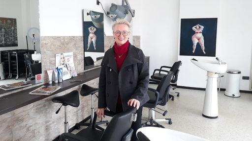 Eine Frau steht in einem Friseur-Salon an einen Stuhl gelehnt.