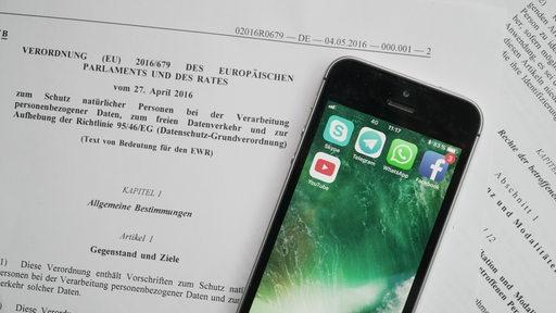 Europäische Datenschutzverordnung mit einem Smartphone, auf denen soziale Apps zu sehen sind
