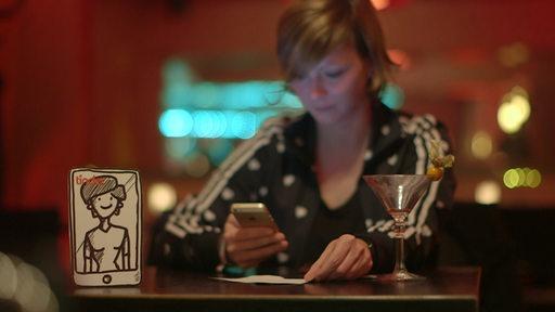 Eine Frau in einer Bar schaut auf ihr Smartphone
