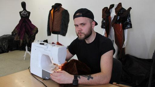 David Koslowski sitzt in seinem Studio an der Nähmaschine