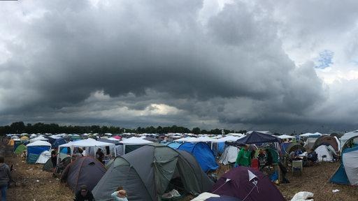 Dunkle Wolken ziehen über den Campingplatz des Deichbrandes auf.