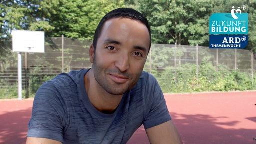 Ein junger Mann stützt sich auf ein Geländer und blickt in die Kamera.