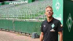 Trainer Markus Anfang steht am Ausgang des Spielertunnels im leeren Weserstadion und schaut hoch auf die Ränge.