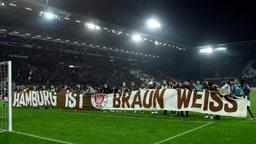 """Spieler des FC St. Pauli halten ein Banner mit der Aufschrift """"Hamburg ist braun-weiss"""" vor den Fanblock."""