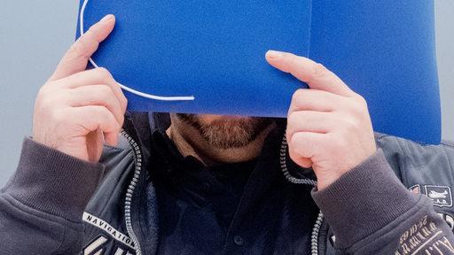 Der angeklagte Niels Högel hält sich eine blaue Mappe vor das Gesicht.