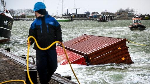 Ein Mann hält ein gelbes Seil, das an einem Container befestigt ist, der im Hafenbecken schwimmt