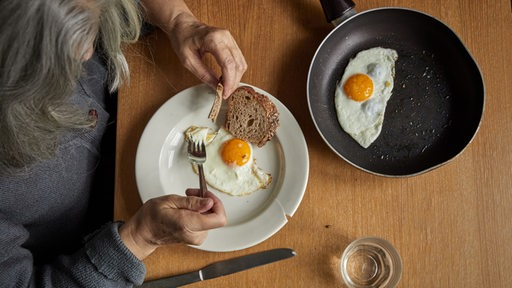 Eine ältere Frau ist Spiegeleier mit Brot.