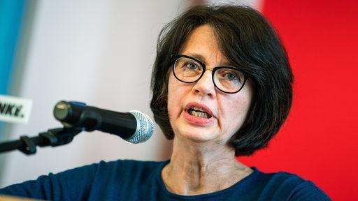 Die Senatorin für Gesundheit, Frauen und Verbraucherschutz Claudia Bernhard steht vor einem Mikrofon und redet.