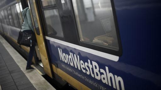 Eine Bahnreisende steigt in Verden in eine Nordwestbahn nach Bremen ein