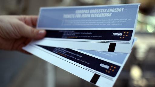Eine Hand hält zwei Konzertkarten. | DPA/Britta Pedersen