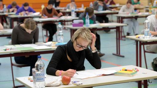 Schüler lesen in der Sporthalle ihres Gymnasiums die Aufgabenstellung ihrer Abiturklausur.
