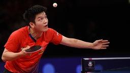 Der Chinese Fan Zhendong schaut beim Aufschlag konzentriert hoch auf den Ball.