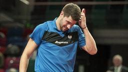 Patrick Franziska kratzt sich mit seinem Tischtennisschläger am gesenkten Kopf.