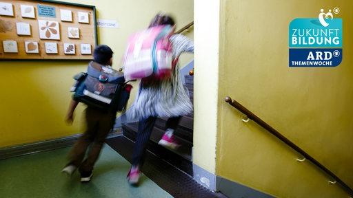 Zwei Schulkinder aus der vierten Klasse einer Grundschule laufen in den Klassenraum (Symbolbild)