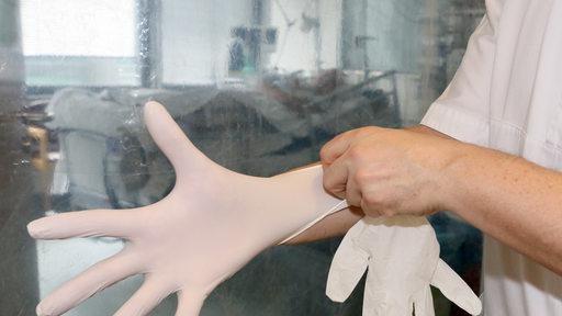 Mensch zieht sich Gummi-Handschuhe an