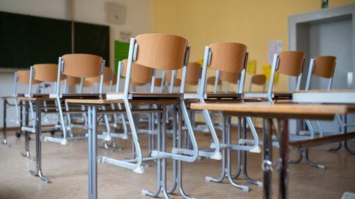Stühle stehen in einem Klassenzimmer auf Tischen.