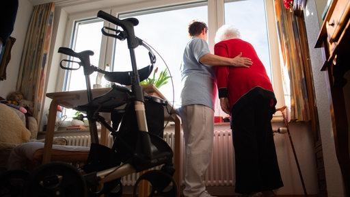 Mitarbeiterin in einem Pflegeheim mit Seniorin