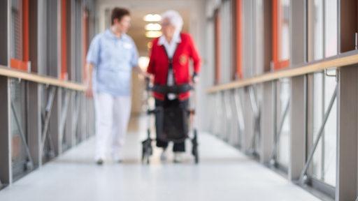 Eine Pflegerin geht mit einer Bewohnerin des Pflegeheims und einem Rollator über den Flur. (Symbolfoto)