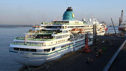 Ein Kreuzfahrtschiff liegt an einer Kaje.