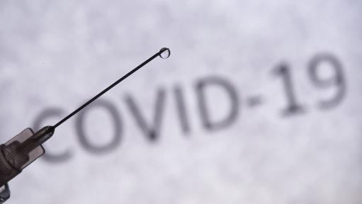 Eine Spritze, an der ein Tropfen hängt, im Hintergrund ein Schriftzug