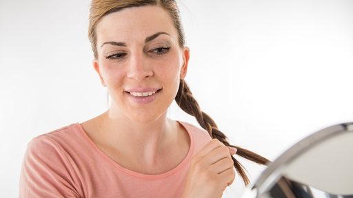 Eine Frau flechtet sich die Haare.