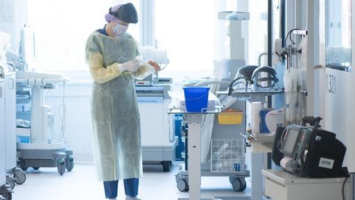 Eine Gesundheits- und Krankenpflegerin, zieht sich auf einer Corona-Intensivstation Einweghandschuhe an. (Symbolbild)   DPA/Sebastian Kahnert
