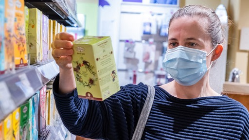 Eine Frau beim Einkaufen mit Hygienemaske über Mund und Nase.