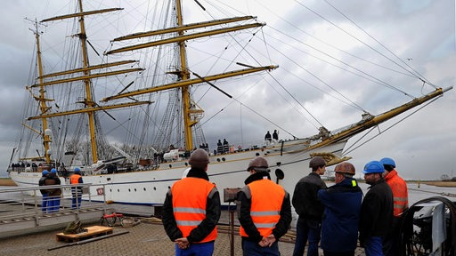 Werftarbeiter schauen auf ein großes Segelschiff